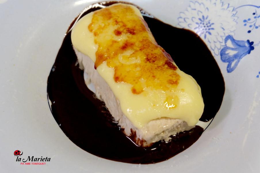 Helado de turrón cubierto de crema y rodeado de chocolate